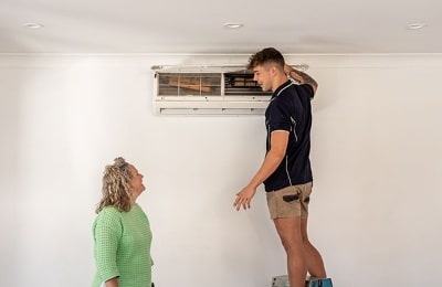 Air conditioning specialist with a customer | Dawson Electric